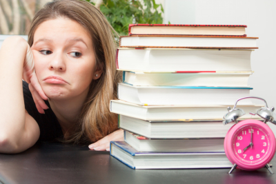 A young woman glances sideways at the large pile of books for exam study time